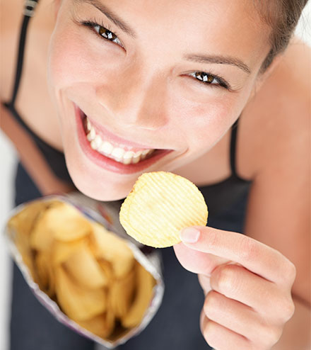 Happy employee eating a big of chips for a snack